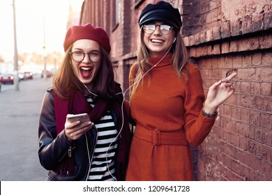 Two joyful young girls dancing while listening to music on smartphone, city outdoor