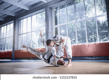 Two judo fighters showing technical skill while practicing martial arts in a fight club. The two fit men in uniform. fight, karate, training, arts, athlete, competition concept