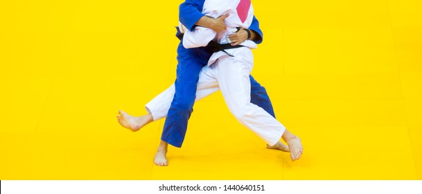 Two judo fighters in white and blue uniform.