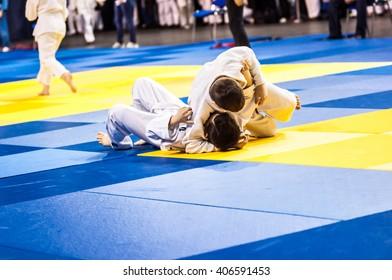 Two judoka in kimono compete on the tatami.