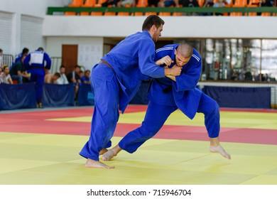 Two judokas in blue judogis fighting