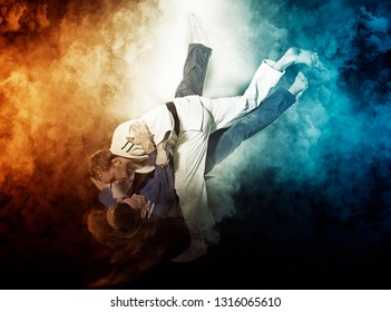 The two judokas fighters fighting man on smoke background