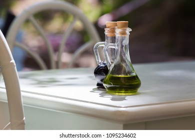Two jugs, with olive oil and balsamic vinegar on the wooden table. Beside are two chair. On the backgoung is nature.