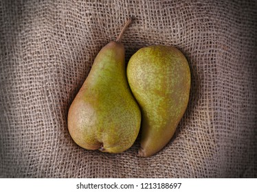 two juicy pears together in a cuddling shape on burlap or Hessian material