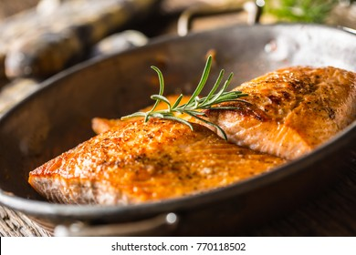 Two juicy salmon steaks in roast pan with herb decoration.