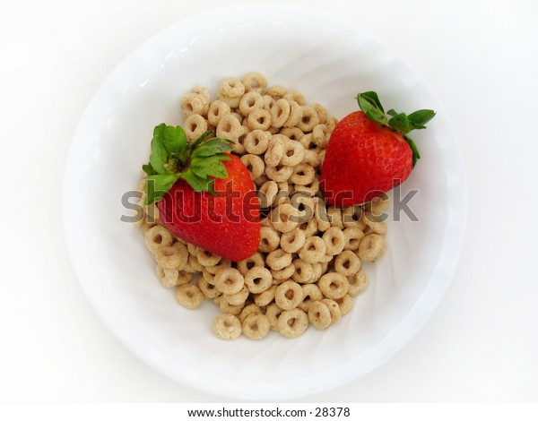 Two juicy strawberries in a bowl of cereal o's. High key, Focus on all subjects.