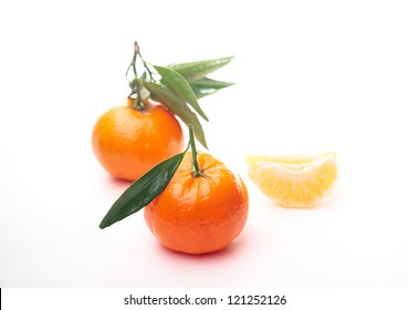 Two juicy  tangerines with green leaves and small  tangerines slice. On a white background