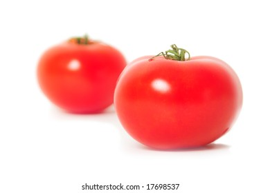 Two juicy tomatoes isolated on a white background