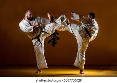 Two karate men fighting in a indoor dojo. With the word kyokushinkai on the background. Which means: the last truth associated.