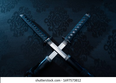 Two katanas, partially drawn blades on fabric with symbols