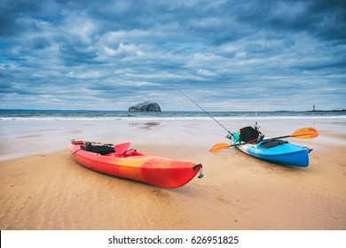 Two kayaks on the beach with the iconic Bass Rock at the background. Near North Berwick, Scotland, UK