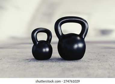 Two kettlebells, small and big, on heavy concrete floor.