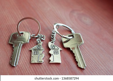 Two keys with splitted broken key rings with pendant in shape of house divided in two parts on wooden background with copy space. Dividing house at divorce, division of property real estate heritage.