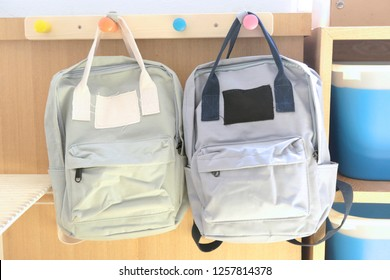 two kid backpacks hanging with hook on the wall in a classroom of kindergarten school