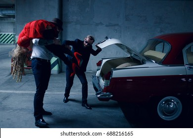 Two kidnapping men abductions a young long haired blonde woman, holding her on the shoulder and puts her inside a car trunk of a white vintage car at the dark underground parking. Horizontal view.