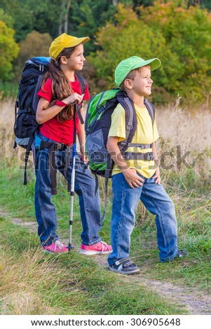 Two Kids Backpacks Traveling Through Meadow Stock Photo Edit Now