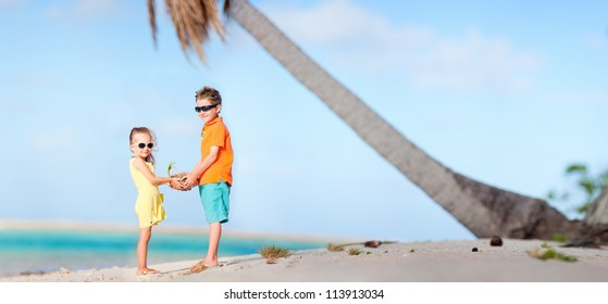 Two kids at the beach holding holding small coconut sprout