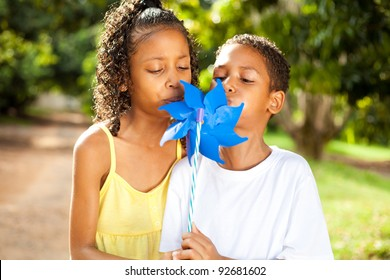two kids blowing on a pinwheel together
