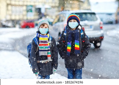 Two kids boys wearing medical mask on the way to school. Children with backpack satchel. Schoolkids on cold winter day with warm clothes. Lockdown and quarantine time during corona pandemic disease