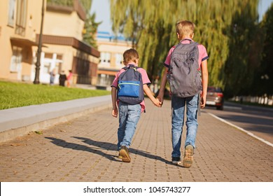 Two kids brothers with backpack holding on hands walking to school in sunny day. Back view.