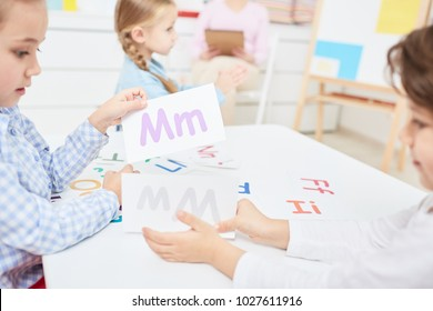 Two kids choosing paper cards with english letters during lesson in kindergarten or elementary school