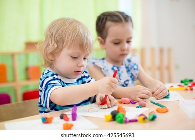 two kids doing arts and crafts in day care centre