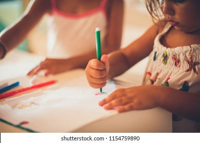 Two kids drawing together. Close up. Copy space. Focus is on hands.