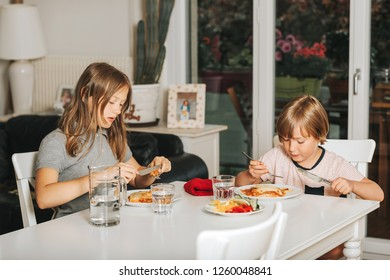 Two kids eating lasagna for lunch, healthy home made meal for children