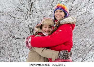 Two kids embracing together on winter forest, outdoors vacation
