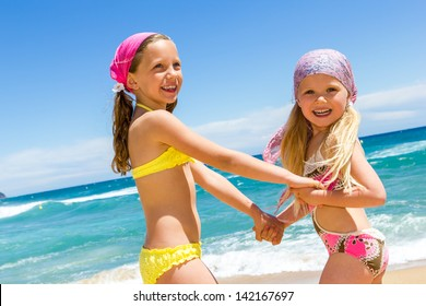 Two kids enjoying a day at the beach together.