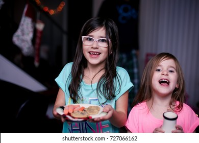 Two kids are excitedly preparing cookies, milk and carrots for Santa and his reindeer on Christmas Eve.
