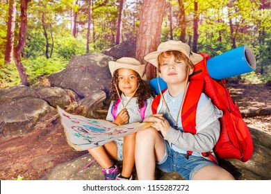 Two kids in forest navigate with map treasure hunt