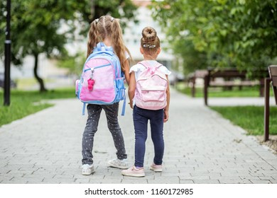 Two kids go to school with backpacks. The concept of school, study, education, friendship, childhood