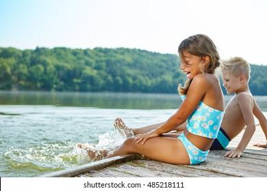 Two kids having fun splashing water with their feet in summer