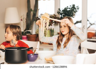 Two kids having spaghetti lunch at home