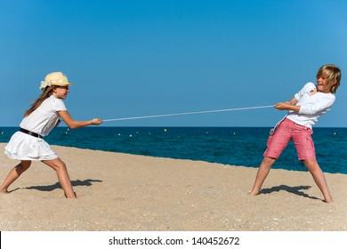 Two kids having a tug war on the beach.