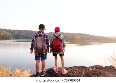 Two kids hiking with backpacks walking studying the route map in a sunny summer day on a forest, Relax time on holiday concept travel, Thailand.