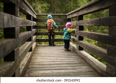 two kids hiking watching waterfall from wooden view platform in austrian alps near krimm