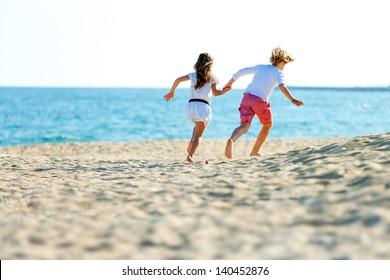 Two kids holding hands running away on sandy beach.