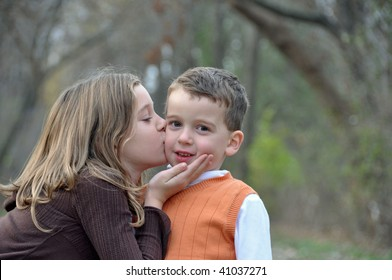 two kids kiss while on a walk in autumn