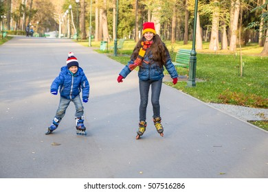Two kids learning to ride in autumn park on roller skates together
