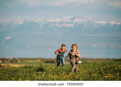 Two kids, little brother and big sister, playing together outdoors in swiss fields with view on lake Geneva and french mountains Haute-Savoie. Image taken in Lausanne area, canton of Vaud, Switzerland