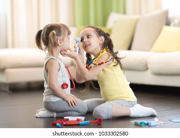 Two kids little girls playing doctor in the living room