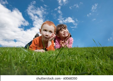 Two kids lying on top of grassy hill with blue sky background