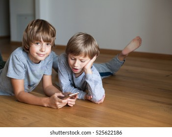 Two  kids lying on wooden floor and using mobile phone