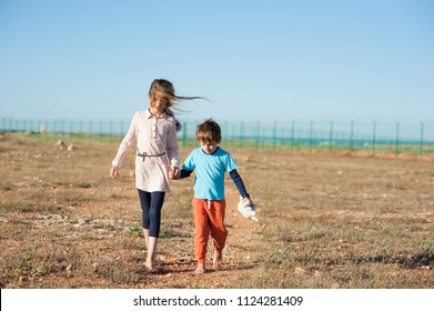 two kids migrants walking in desert shoeless with plush toy along state border fencing