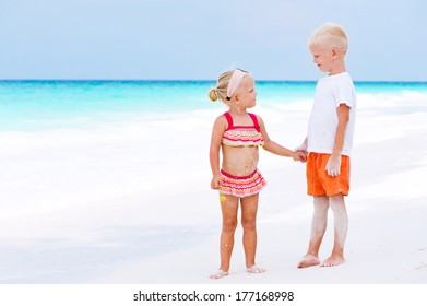 Two kids on tropical white beach during summer vacation