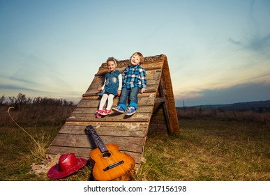 two kids on a wooden meadow construction at fall sunset