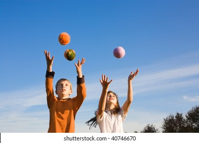 Two kids are playing balls outdoor