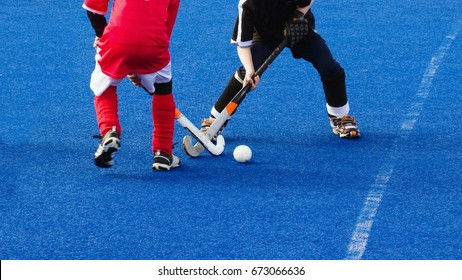 Two kids playing field hockey in cold weather on wet turf